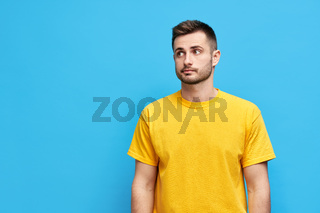 Doubtful thoughtful man looking aside to copy space over blue background