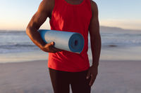Mid section of senior african american man holding yoga mat at the beach