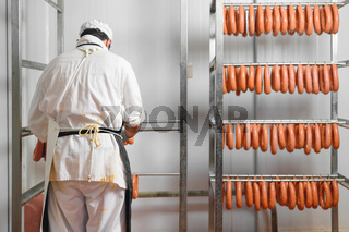 Worker hangs raw sausages on racks in storage room at meat processing factory