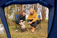couple cooking food on gas burner at tent camp