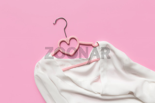Black Friday or clothing industry concept, pink background, hanger, white blouse