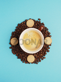 Cup of tasty coffee on coffee beans with cookies turns clockwise