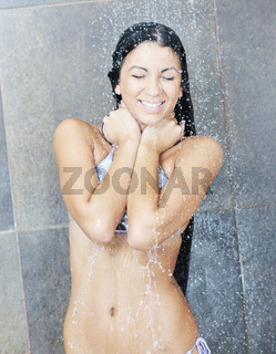 sexy young woman enjoing bath under water shower