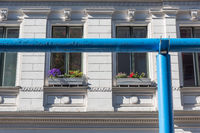 Old house with colorful flower boxes and a blue water pipe