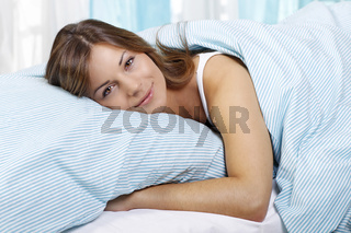Young woman in bed with her arms around a pillow,Junge Frau liegt im Bett,Junge Frau liegt entspannt im Bett
