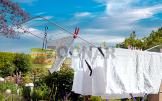 Drying rack on sunny day for drying white clothes. Collapsible clothes horse with clothes