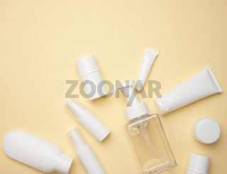 top view of white cream tubes, cosmetic dispenser, empty jars and with hand cream, transparent dispenser on a light yellow background. Branding of cosmetic products, mock up