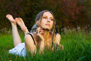 Beautiful woman lying on a grass