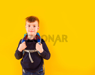 the little pupil wearing style clothes stands with folded arms