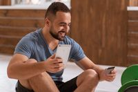 Cheerful man with smartphone and debit or credit card buying online equipment or doing sport bets and gambling online. Modern digital sports life. Sport app on smartphone. Cash app. Banking app