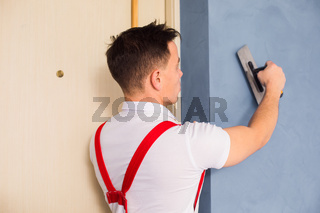 the plasterer is aligning wall using a special tool