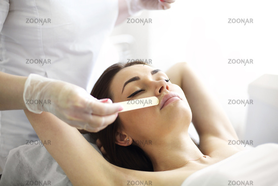 Crop beautician applying acid peeling in salon