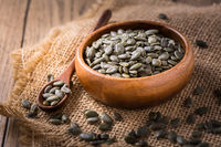 Organic pumpkin seeds in bowl on wooden background