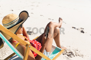 Mixed race woman on beach holiday sitting in deckchair using smartphone