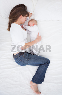 Brunette woman lying next to her baby
