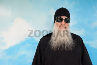 Portrait of mature man with long gray beard against blue sky and cloud background wall outdoors with copy space