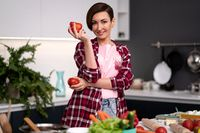 Holding bell pepper and tomato in the hand housewife wearing plaid shirt with a short hairstyle cooking vegetable ragout at new kitchen in new house. Healthy food at home