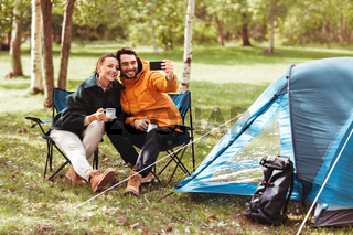 couple drinking tea and taking selfie at tent camp