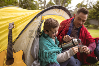 Caucasian father and pouring coffee in a cup for his son while sitting in a tent in the garden