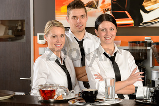Three server posing in uniform in cafe