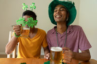 Smiling mixed race gay male couple wearing st patrick's day costumes drinking beer
