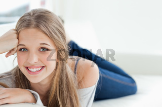 Smiling girl lying on the couch as she looks at the camera