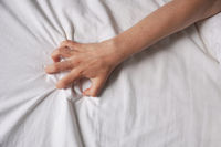 female hand grabs bed sheet
