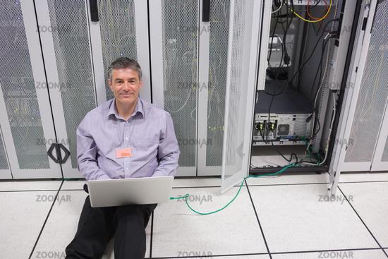 Smiling man doing server maintenance with laptop