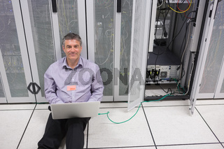 Smiling man doing server maintenance with laptop