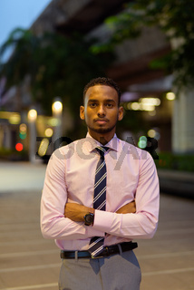 Young African businessman outdoors in city at night with arms crossed