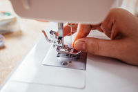Closeup hands inserting thread into sewing machine needle