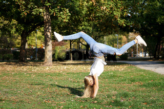 girl praticing handstand in a park