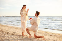 man with ring making proposal to woman on beach