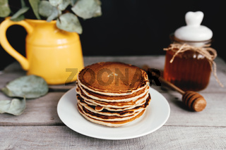 Pancakes with honey on plate, wooden table, spoon, yellow vase with eucalyptus