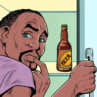 a black african american man near the refrigerator with beer. Alcohol addiction