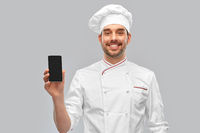 happy smiling male chef showing smartphone