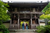 Visitors looking at the gate entrance with nio kings statues at Daisho-in temple in Miyajima, Japan