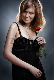 Attractive smiling young woman with rose