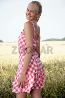 Junge Frau mit blonden Haaren im Kornfeld
