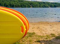 Stack of yellow and orange paddleboards on sandy beach by a lake