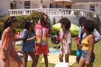 Diverse group of friends drinking and talking at a pool party