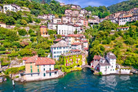 Town of Nesso on steep cliffs and creek waterfall on Como Lake aerial waterfront view