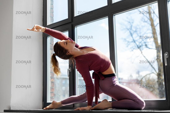 woman doing yoga exercise on window sill at studio