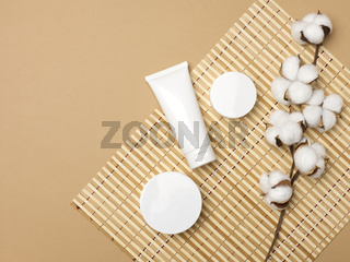 jar and empty white plastic tubes for cosmetics on a beige background. Packaging for cream, gel, serum, advertising and product promotion, mock up
