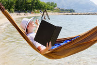 Work from anywhere. Young smilyng woman, female freelancer in straw hat working on laptop on beach.