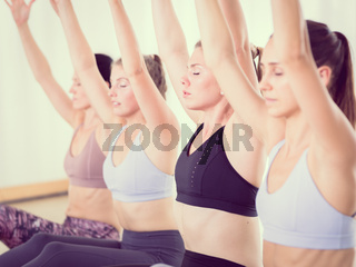 Group of young sporty attractive women in yoga studio, practicing yoga lesson with instructor. Healthy active lifestyle, working out indoors in gym
