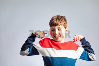 the smiling boy with raised hands demonstrates his muscular