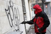 Worker cleaning graffiti