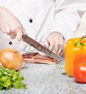 chef cutting bacon
