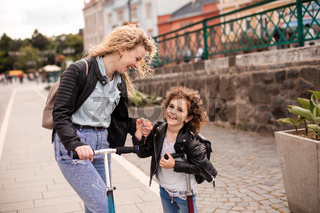 Identical mom and daughter with scooters in the city